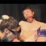【ゲイ動画】M字開脚をさせられながら拘束されているケツ毛がボーボーな男がゴーグルマンにもてあそばれることになる!